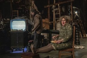 cast members on stage sitting in a cluttered room with ladders and a very old Television