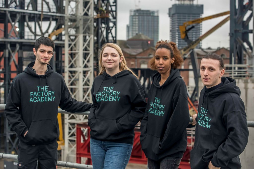 Four young people wearing jumpers emblazoned with the words 'The Factory Academy' stood with The Factory construction site in the background