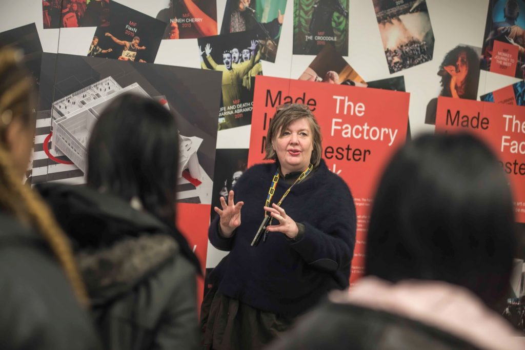 Emma King speaking to students with posters of The Factory and past MIF events behind her