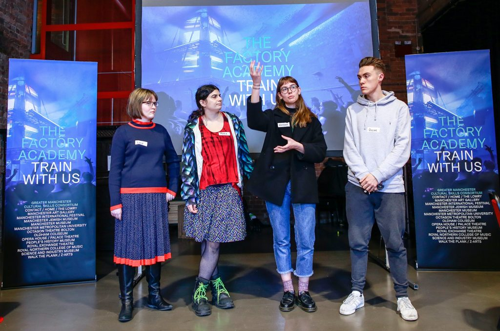 Four young stood people presenting in front of The Factory Academy banners