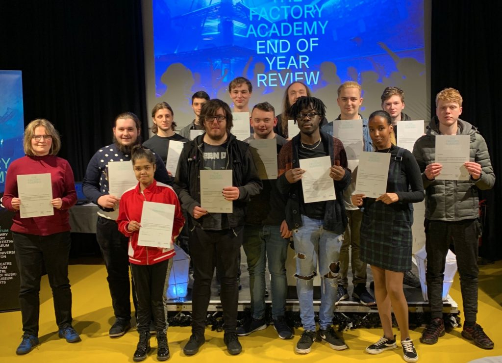 14 people aged between 16 - 24 holding up certificates in front of a screen that says Factory Academy End of Year Review