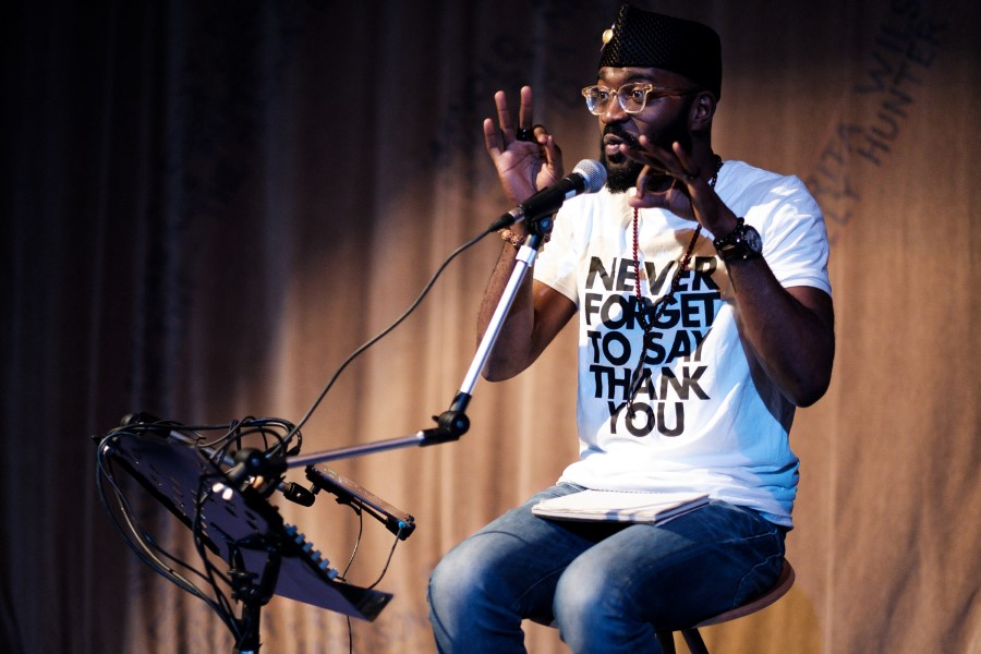 Inua Ellams sat on a stool. He's talking into a microphone, has his hands raised almost to his face making an 'OK' gesture with both hands. He's wearing a white t-shirt with 'NEVER FORGET TO SAY THANK YOU' emblazoned across it.